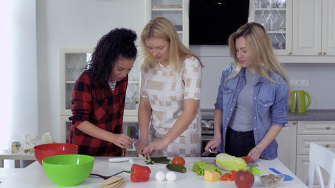 Curly brunette comes to her friends at the kitchen and tries cucumber for salad Footage