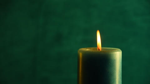 Teal candle trembling flame out of the green and blown out 영상물