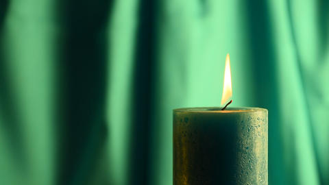 Teal candle trembling flame with green curtain background and blown out Footage