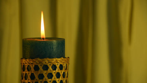 Teal candle trembling flame with yellow curtain background and blown out Footage