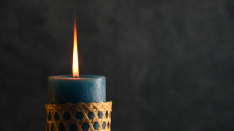 Blue candle trembling flame with grey background focusing in and blown out Footage
