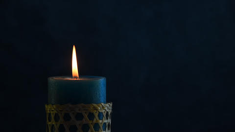 Blue candle trembling flame with blue background blown out Footage