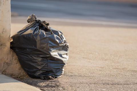 Black garbage bag lies on the road Photo