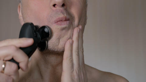 Man shaving beard with electric shaver. Closeup Image
