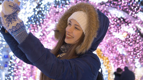 A young girl does selfie on a smartphone. Against the background of festive 영상물
