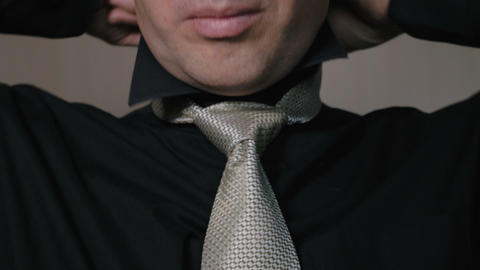 The man straightens the knot of his tie. Businessman going to work in the Footage