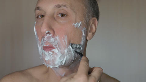 Man shaves his face. Man shaving with foam and manual razer Footage
