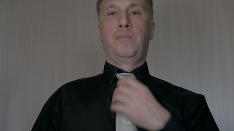 A man tie a knot on a tie. Going to work. Black shirt Stock Video Footage