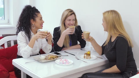 Three happy girlfriends relaxing in cafe with coffee and sweets Footage