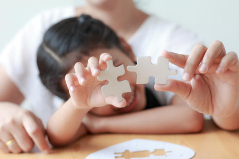Asian little girl playing jigsaw puzzle with her mother for fami Photo