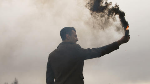 Serious man holding smoke bomb with black fume 영상물