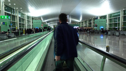 Women with roll-aboard bag come to travolator, dim interior of BCN terminal Footage