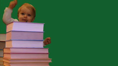 cute smiling 1 year old baby standing near books pile green screen vertical Footage