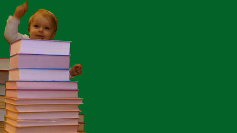 cute smiling 1 year old baby standing near books pile green screen Footage