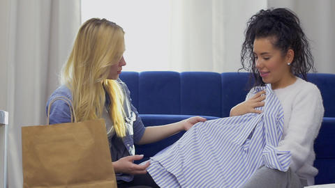 Two young women shows each other a purchased clothing after shopping in the mall Footage
