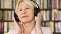Cheerful senior woman listening music with wireless headphones. Pensioner Footage