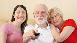 Senior couple and teen daughter watching TV. Switching channels. Happy family Footage