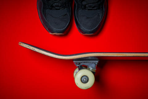 shoes and used skateboard on a red background Foto