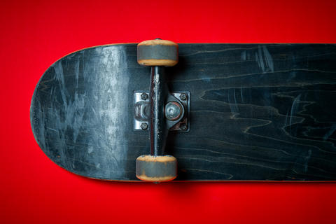 used skateboard on a red background Fotografía