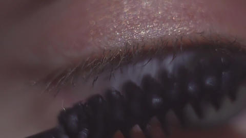 Green eyed woman applying black make up mascara on eyelash Footage
