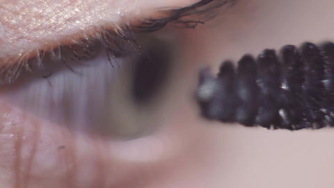 Green eyed model applying black cosmetics mascara on eyelash Footage