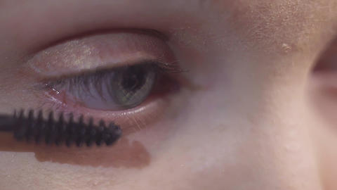 Green eyed woman puts black cosmetics mascara on eyelash Footage