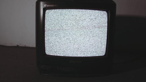 Old style television set static screen on floor in dark room flashing light Live Action
