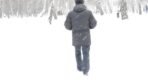An elderly man in a black jacket and hat walks during snowfall in winter Park Footage