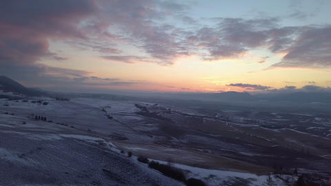 Aerial view of evening sunset color over snowy fields Footage