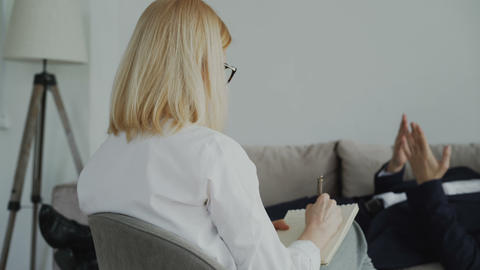 Pan shot of Psychotherapist or psychologist writing notes while talking with Footage