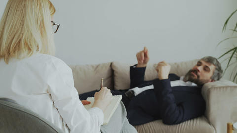 Psychotherapist or psychologist writing notes while talking with businessman Footage