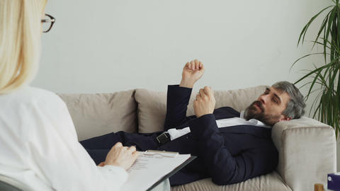 Man lying on sofa talking about his problems with professional female Footage