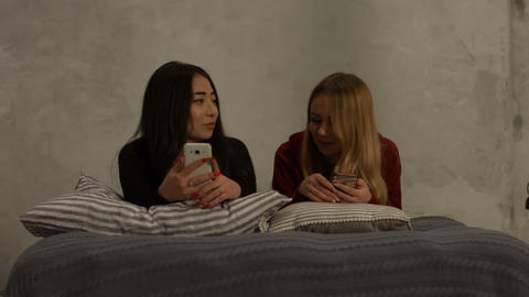 Diverse girlfriends busy with smart phones at home Live Action