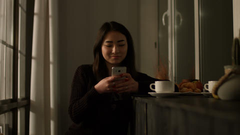 Smiling asian girl typing message on smart phone Live Action