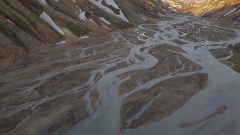 Tilt up from river delta to Icelandic snowy mountains Footage