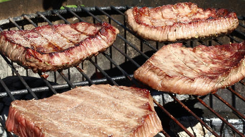 Grilled beef steaks cooking on barbecue grill Footage