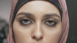 Young beautiful girl in pink hijab looking at camera. Portrait, close-up of eyes Footage