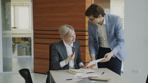Two business colleagues discussing reports in modern office. Businesswoman Footage