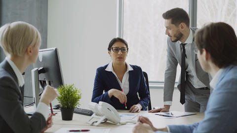 Businesswoman talking with male and female colleagues sitting at the table in Footage