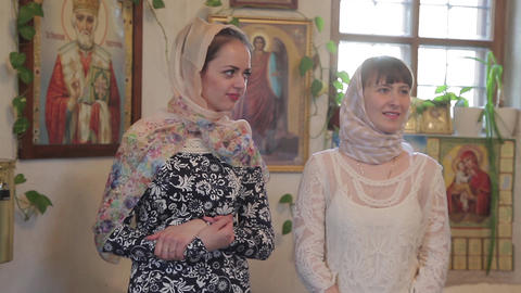 two young women in headscarves in the Church communicate Footage