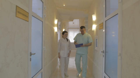 Two doctors leave the office walk down the corridor and discussing Footage