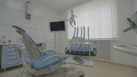 Contemporary empty dental office with dental chair and equipment Footage