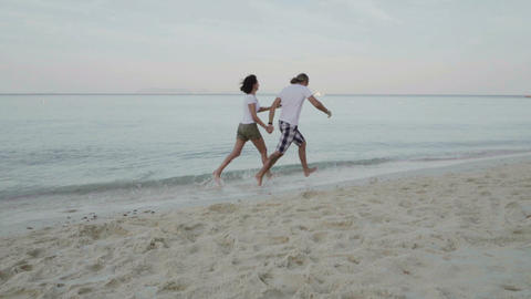 man and woman running on the exotic beach Footage