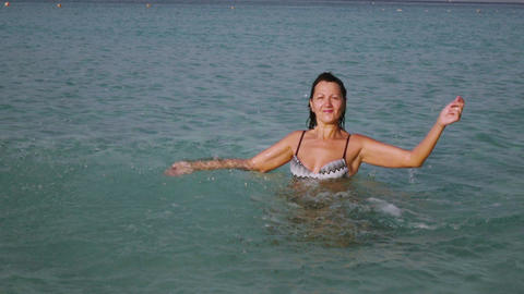 woman playing with sea water at beautiful sunrise Footage