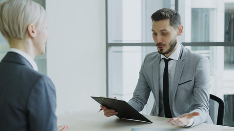 HR male manager shaking hand to female candidate after having job interview in Footage