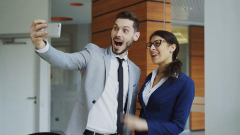 Happy businessman and his female colleague taking a selfie on smarphone camera Footage