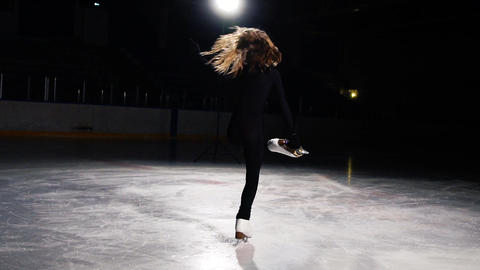 A beautiful figure in a black suit makes a rotation around her axis in slow Footage