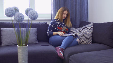 Beautiful young girl wearing sweater is relaxing on sofa with journal Footage