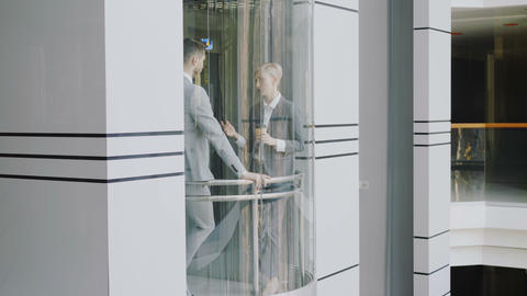 Tilt down of businesswoman and businessman colleagues talking in moving elevator 영상물