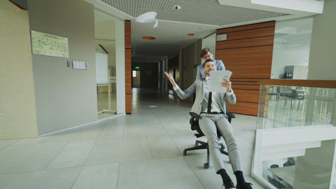 Dooly shot of Two crazy businessmen riding office chair and throwing papers up Footage